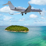 Jet over the tropical island Stock Images