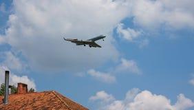 Jet-Passagier-Flugzeugfliegen über Dach lizenzfreie stockbilder