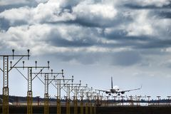 Jet plane / aircraft landing on the runway. Lights at the runway at an airport royalty free stock images