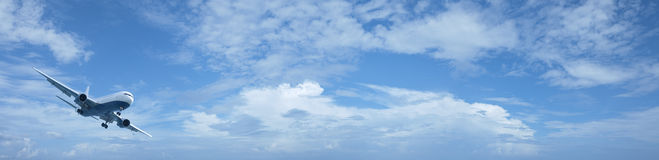 Jet plane in a blue cloudy sky Royalty Free Stock Photos