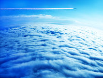 Jet plane contrail in blue sky above the clouds Royalty Free Stock Photography
