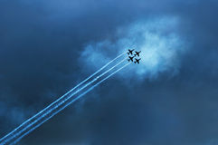 Jet plane display team. Four jet planes, part of a display team,  climbing through cloud  in formation leaving vapour trails Royalty Free Stock Photo