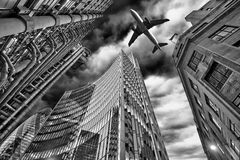A jet plane flying over the city stock photography