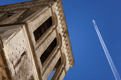 Jet plane flying over historic bell tower Stock Photos