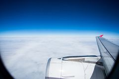 Jet plane flying over white cloud and clear blue sky above Royalty Free Stock Images