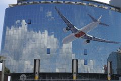 Jet plane, sky reflection on windows, modern building. Royalty Free Stock Photography