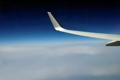 Jet plane wing on the background of thick clouds Royalty Free Stock Image