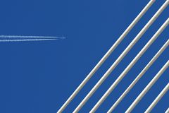 Free Jet Plane With Trace & White Bridge On Blue Sky. Royalty Free Stock Images - 117928009