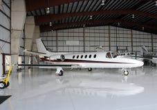 Jet privado en hangar Imagenes de archivo