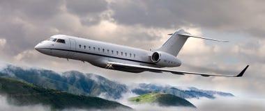 Jet privado que vuela sobre las montañas Imagenes de archivo