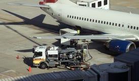 Jet que reaprovisiona de combustible en el aeropuerto Foto de archivo