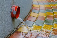 Water flows down the sidewalk along a drainpipe during spring rain. royalty free stock photos