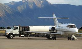 Jet refuel. Private jet receiving fuel from tanker truck Stock Photos