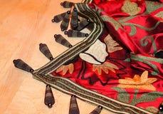 Jet richement coloré brodé avec les bracelets uniques astucieusement montrés sur le fond en bois photos libres de droits