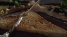 A jet of sauce falls on the toast. A stream of mayonnaise pours on the bread. Slow motion pouring white sauce on toast. Close-up stock video