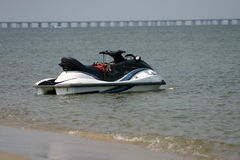 Jet ski. Lone jetski floating in the water with a bridge in the background stock photography