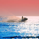 Jet ski. Person jet skiing on sparkling blue waters under a red sky at sunset Royalty Free Stock Image