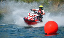 Jet Ski competitor cornering at speed creating at lot of spray. WYBOSTON, BEDFORDSHIRE, ENGLAND -  APRIL 09, 2017: Jet Ski competitor cornering at speed Royalty Free Stock Images