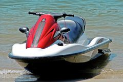 Jet ski front view. A jet ski pulled up onto a sunny beach Stock Image