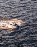 Jet ski going fast in the waters of the Stockholm archipelago at the sunset, Sweden stock photography