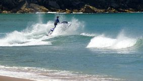 Jet ski jumps wave. A jetskier jumps a wave off a beach sending alot of spray and foam into the air Royalty Free Stock Image