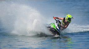 Jet Ski konkurrent som tränga någon på hastighet som skapar på lotten av sprej Royaltyfri Fotografi