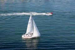 Jet Ski Passing Sailboat foto de archivo libre de regalías