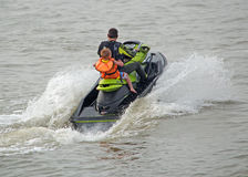 Jet ski power fun family. Photo of jet ski man and son enjoying high powered fun on the ocean at herne bay seafront on 21st april 2014 and ideal for water sports Royalty Free Stock Photo