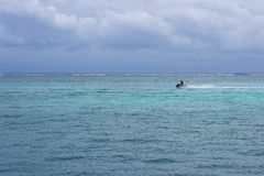 A jet ski races across the Caribbean inside the Meso-American reef. San Pedro, Belize Stock Photography