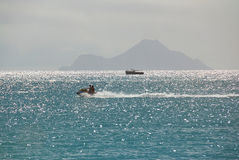 Jet ski ride on caribbean island. With island on background sunny day Royalty Free Stock Images