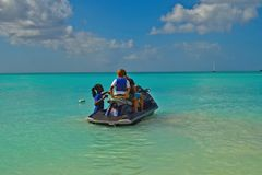 Jet ski rider in turquoise water off Antigua. Jolly Beach, Antigua - January 2015: local man gives advise to two jet ski riders Stock Photos