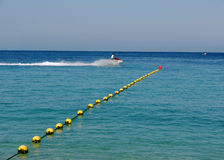 Jet ski speeding on calm water. A jet ski speeding on blue calm ocean leaving white wake behind. Yellow buoys mark the swimming domain ending with a larger red Royalty Free Stock Image