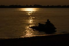 The jet ski with sunset in evening and the lagoon in thailand.  Royalty Free Stock Image