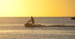 Jet skier. Trearddur Bay sunset with the a jet skier playing in the last rays of the sun Royalty Free Stock Photo