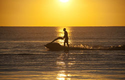 Jet skier. Trearddur Bay sunset with the a jet skier playing in the last rays of the sun Royalty Free Stock Images