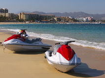 Jet skis on the beach. Red and white jet skis on the beach waiting for customers. Hotels and mountains in the background, Cabo San Lucas Baja Sur Mexico Stock Photo