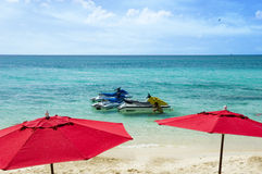 Jet skis in paradise. A Caribbean resort offers jet skis and red umbrellas to entertain and shade their guests Royalty Free Stock Photos