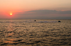 Jet skis in the sea at sunset Royalty Free Stock Photos