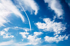Jet smoke and blue sky. Jet smoke and deep blue sky with white clouds Royalty Free Stock Image