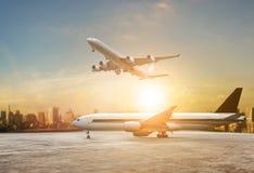 Jet som flyger över landningsbanor och härlig dunkel himmel med kopian arkivbild