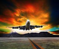 Jet som flyger över landningsbanor och härlig dunkel himmel med kopian arkivfoto