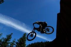 Jet Stream Drop. Mountain Biker jumps off railway car Stock Photos