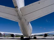 Jet Tail. Wide angle view of the tail end of a four engine jet plane against a deep blue sky Royalty Free Stock Image