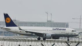 Lufthansa Airbus A320-200 D-AIUO in Munich Airport, snow. Jet takes off from Munich Airport, Germany, winter time with snow on runway. Flughafen München stock video footage