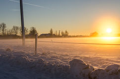 Jet trails and a golden sunset on a snowy field Royalty Free Stock Images