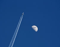 Jet with vapor trail. Passes the moon at a deep blue sky Stock Photos