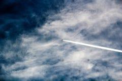 Jetbladeren achter een witte chemtrail in de hemel stock foto