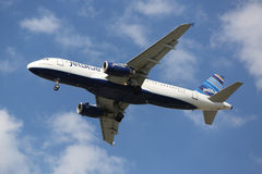 JetBlue Airbus A320 descending for landing at JFK International Airport in New York Stock Photography