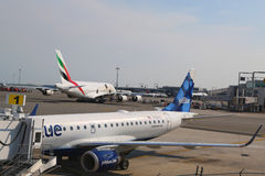 JetBlue Embraer 190 aircraft at the gate at the Terminal 5 and Emirates Airline Airbus A380 at JFK International Airport Stock Images