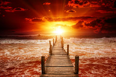 Jetée pour des bateaux dans la mer Lever de soleil lumineux au-dessus de l'océan Photo stock